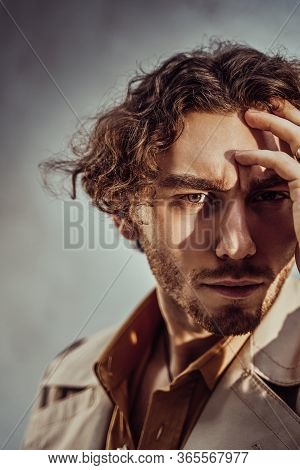Thoughtful And Handsome Young Man Posing In A Bright Studio On A White Background, Looking Focused W