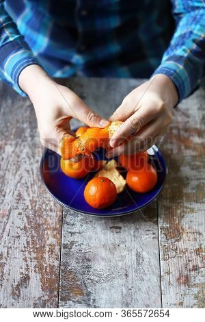 Selective Focus. Peeling Tangerines. Men\'s Hands Are Peeling Mandarin. Tangerines In A Plate.
