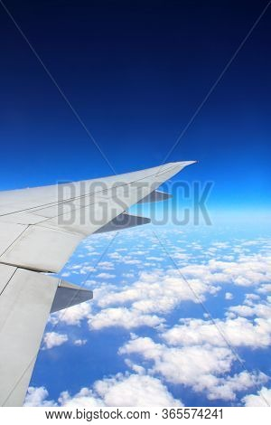 Traveling concept. Aerial view of cloudscape. Looking Out the Window of a Plane. Scenic view with wing of an airplane. Copy space for text