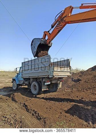 Excavator Machine Loading Soil Into Truck Body By Scoop. Modern Loading Equipment. Fertile Soil Tran