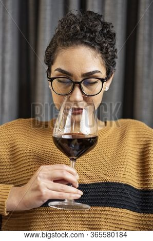 A Woman Wearing Glasses And A Sweater Smelling Red Wine