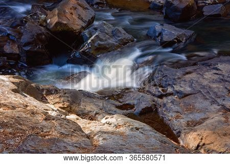 Water Intentionally Blurred By Slow Camera Shutter Speed Flowing Softly Over Rocks On A Creek Bed