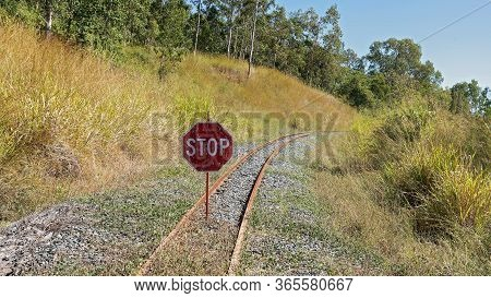 Red And White Stop Sign In The Middle Of Unused Railway Tracks In The Country