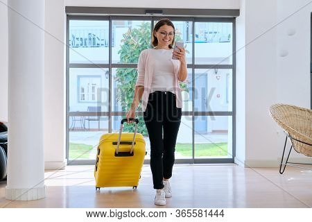 Woman Tourist Hotel Guest With Suitcase In The Lobby Of Hotel Using Smartphone. Travelling, Vacation