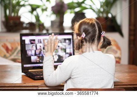 Distance learning-online education. School girl watching online education classes and doing school homework. COVID-19 pandemic forces children online learning.
