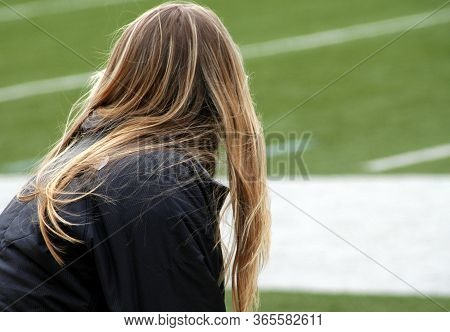 Head Cheerleader Watching Her Team In Formation On The Football Field.