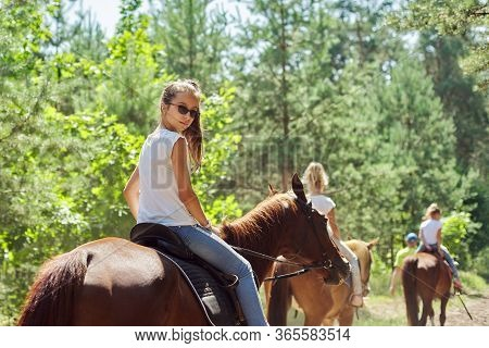 Teenager Girl Riding A Brown Horse, Horseback Riding For People In The Park.