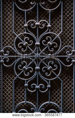 Metal Forging On Door, Blue, Against The Background Of Small Mesh Of Slave. Elements Of Architectura
