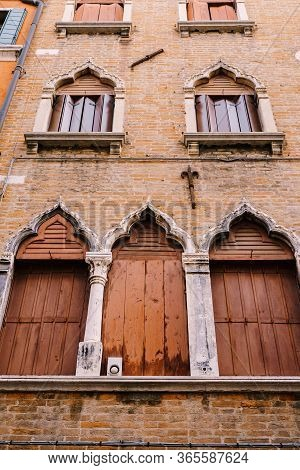 Windows Of Venice Are A Building Of Several Floors, Made Of Red Brick, Three Windows With Brown Shut