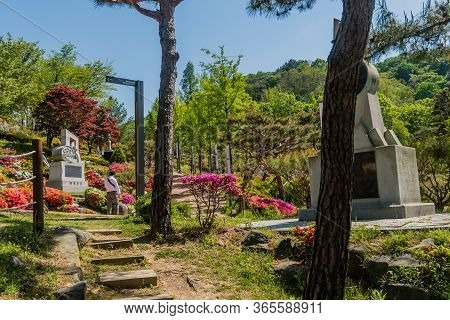 Daejeon, South Korea; May 7, 2020: Man Wearing White Shite Walking Past Sculpted Grave Marker In Ppu