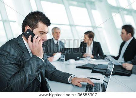Hombre de negocios hablando por teléfono durante la reunión