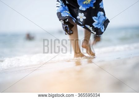 Woman Bare Foot Walking On Summer Beach. Close Up Leg Of Young Woman Walking Along Wave Of Sea Water