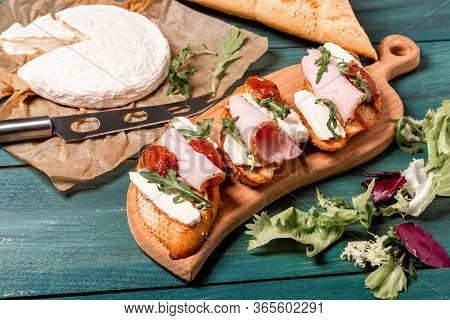 Appetizers Table With Italian Antipasti Snacks. Bruschetta With Brie Cheese, Arugula And Sun-dried T