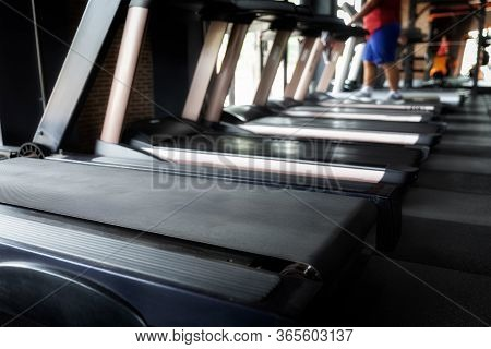 Fat Man Exercising On Treadmill At A Gym.focused On Treadmill.