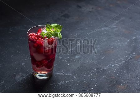 Raspberry Alcoholic Cocktail With Liqueur, Vodka, Ice And Mint On A Dark Background. Raspberry Mojit