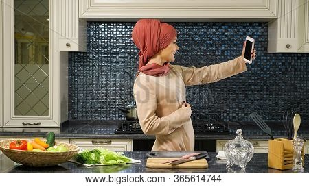 Pretty Oriental Lady In Hijab Stands Half Face And Makes Selfie Against Fresh Organic Food On Table