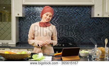 Smiling Lady In Hijab Talks With Relatives On Skype Using Modern Laptop And Cooking Supper In Kitche