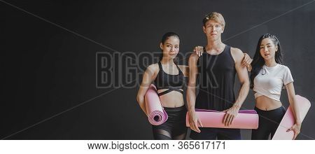 Copy Space Banner. Group Of Young Sporty Multicultural People Slim Body Holding Yoga Mat At Dark Bla