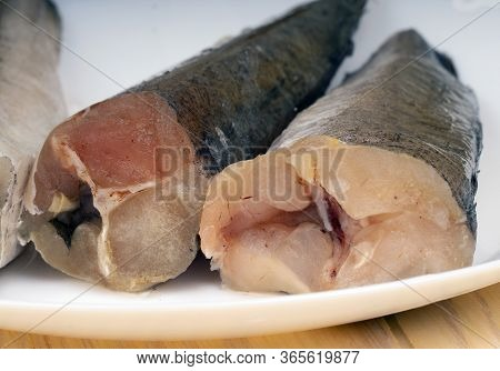 Uncooked Headless Hake Fishes Lie On A Plate, Cropped Image.
