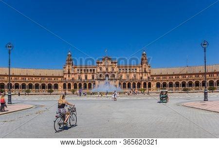 Sevilla, Spain - May 14, 2019: Woman Riding A Bicycle At The Plaza Espana In Sevilla, Spain