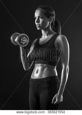 Beautiful Woman Exercising Her Bicep Muscles With A Dumbbell.
