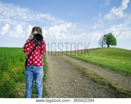 Young Girl With A Big Camera In Rural Switzerland Taking Pictures Of The Scenery.