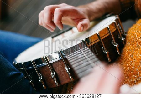 Male Banjo Player Sitting On The Verandah Practicing Banjo Techniques Like Finger Picking, Clawhamme