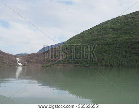 Calm Svartisvatnet Lake And Waterfall On Landscapes Near European Svartisen Glacier In Nordland Coun