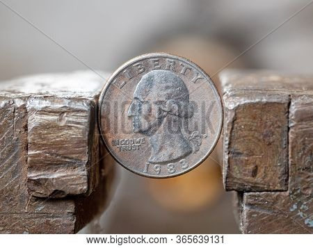 Dollar Coin Clamped In A Metal Vise, Close-up. Currency And Usa Economy Under The Onslaught, The Con
