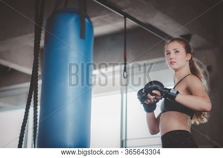 Confident Caucasian Women Posing For Boxing Training In The Fitness Gym With Punching Bag In Backgro