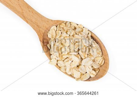 Uncooked Rolled Oats In The Wooden Spoon On A White Background, Top View Close-up