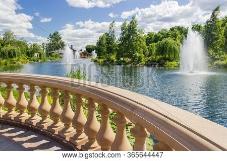Fragment Of Stone Balustrade With Shaped Balusters Over The Decorative Pond With Fountains In Summer