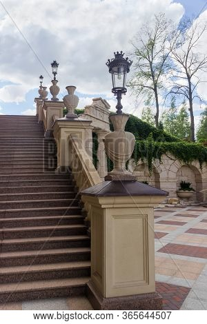 Fragment Of Stone Staircase With Carved Stone Railing And Streetlights Mounted On On Them In Park, B