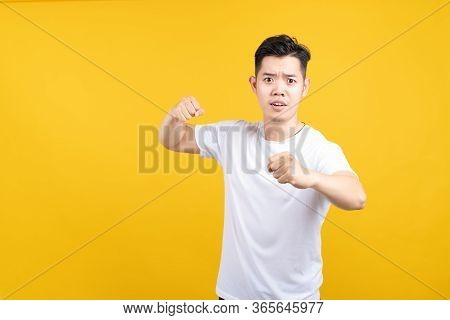 Attractive Young Asian Man Hold Fist Fury And Angry Negative Emotion Wearing White T-shirt On Yellow