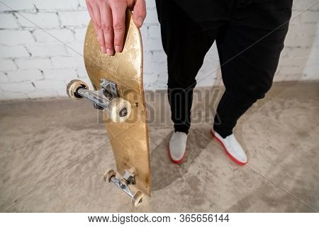 Close Up Of Skateboarder Standing Next To A White Brick Wall. Athletic Teenager Wearing Jeans With A