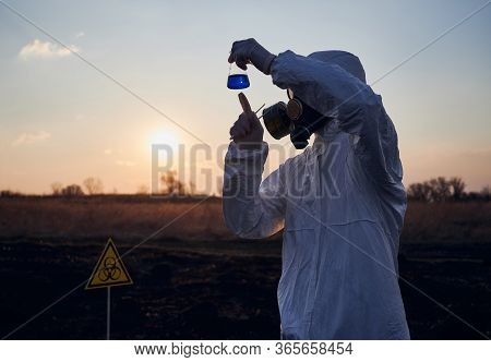 Environmentalist In Suit, Gas Mask, Sterile Gloves Doing Research Work In Field With Burnt Grass, Ho