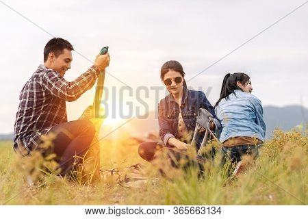 People Pitch A Tent On The Ground Near The Lake At Sunset. Relaxing, Traveling, Long Weeked, Holiday