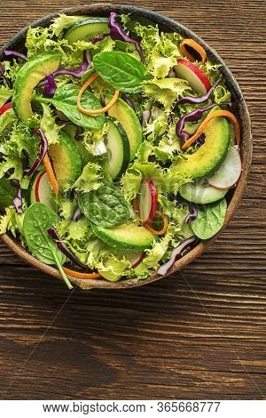 Green Lettuce Salad With Fresh Mixed Vegetables On Wooden Table Background