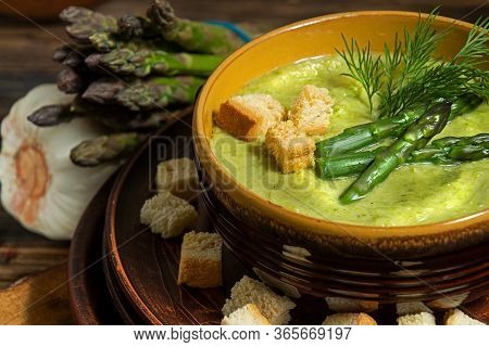 Purred Creamy Asparagus Soup In Glass Bowl On Black Plate Against Raw Fresh Asparagus And Greenery