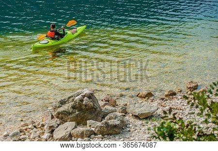 Man On Vacation Enjoying Kayaking In Pristine  And Clean Lake.