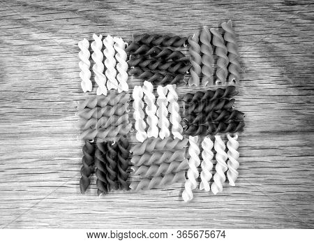 Dry Multi-colored Pasta On Wooden Board In Black And White. Food And Ingredientes Background.