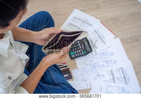 A Businessman Who Is Sitting On The Floor Of The House Opening The Wallet But Have To Pay Debt Calcu
