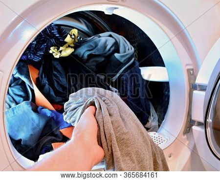 Closeup Of Hand Holding And Put Washed Laundry Into Tumble Clothes Dryer Machine.