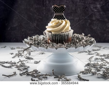 Chocolate Cupcake With White Frosting Piled High And A Black And Silver Polka Dot Prom Dress On Top,