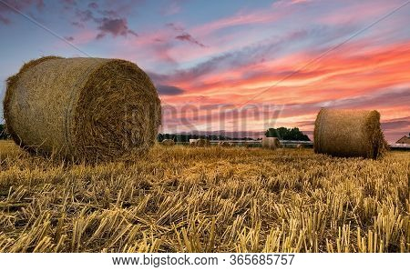 Beautiful View Of A Dramatic Sunset Sky Over Harvested Hay Field With Hay Bales In The Kempen Area,