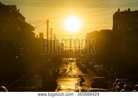 Urban Scene. Cars Stand At The Traffic Light. Silhouettes Riding Bike And Walking On Pedestrian Stre