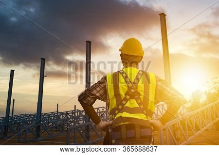 The Construction Engineer Supervises The Construction Site And The Sunset Background