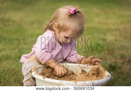 Little Girl Enthusiastically Plays With Mud In A Basin In The Courtyard Of The House. Child Kneads A