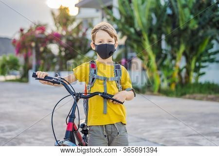 Active School Kid Boy In Medical Mask Riding A Bike With Backpack On Sunny Day. Happy Child Biking O