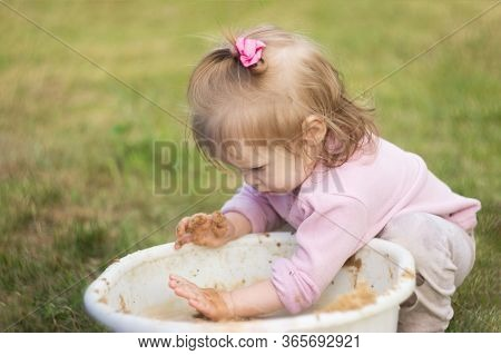 A Little Girl Enthusiastically Plays With Mud In A Basin In The Courtyard Of The House. The Child Pa